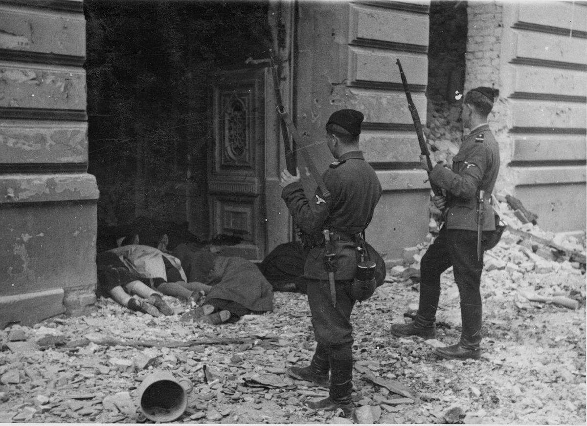 Żołnierze z kolaboranckich jednostek przy zwłokach zamordowanych Żydów w bramie kamienicy przy ul. Kupieckiej 18.